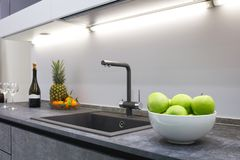The interior of the modern kitchen is illuminated with a gray stone countertop with a luxury washbasin and mixer, fruit pineapple. And tangerines, a bottle with stock image