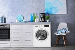 Interior of modern kitchen with washing machine. Laundry day stock photos