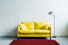 Interior of modern living room with rug, couch and floor. Lamp beside Royalty Free Stock Photo