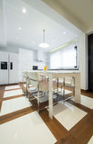 Interior of a modern luxury bright white kitchen with dining tab Stock Images