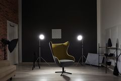 Interior of modern photo studio with armchair. And professional equipment stock photo