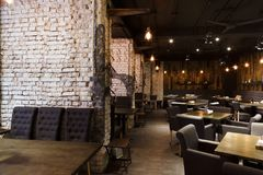 Interior of modern restaurant, loft style. Interior of modern restaurant. Contemporary design in loft style, big cozy hall with tables and private cabins with royalty free stock images