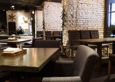 Interior of modern restaurant, loft style. Interior of modern restaurant. Contemporary design in loft style, big cozy hall with tables and private cabins with stock photography