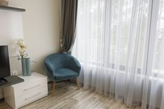 Interior of modern room with comfortable armchair near to large window with sheers and gray curtains royalty free stock photo
