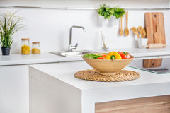 Interior of modern white kitchen with induction cooking heater an vegetables on the  table Stock Photography