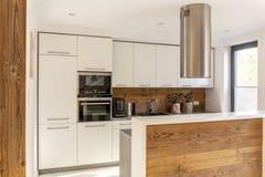 Interior moderno branco da cozinha com a capa de fogão de prata acima da madeira fotografia de stock