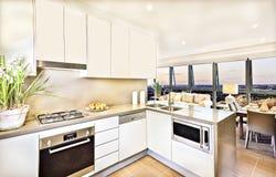 Interior moderno de la cocina con área de la sala de estar en la tarde fotos de archivo
