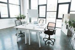 interior moderno de la oficina con el escritorio, papeles, sillas imagen de archivo