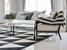Interior moderno de la sala de estar con las almohadas y la alfombra comprobadas blancos y negros del modelo Fotos de archivo