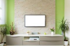 Interior moderno de la sala de estar - la TV montó en la pared de ladrillo con la pantalla blanca fotos de archivo libres de regalías