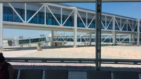 Interior moderno del aeropuerto con los asientos, la ventana grande y el paso superior del vidrio afuera metrajes
