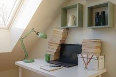 Interior moderno del espacio de trabajo Ordenador portátil y pila de libros foto de archivo libre de regalías