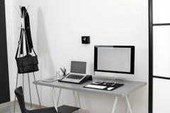 Interior moderno del lugar de trabajo con los ordenadores en la tabla imagen de archivo libre de regalías