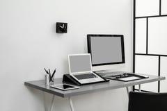 Interior moderno del lugar de trabajo con los ordenadores en la tabla imagenes de archivo