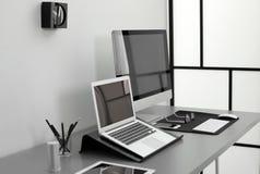 Interior moderno del lugar de trabajo con los ordenadores en la tabla fotografía de archivo