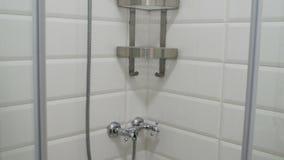 Interior moderno do banheiro Cabine vazia do chuveiro com as paredes e as prateleiras telhadas brancas filme