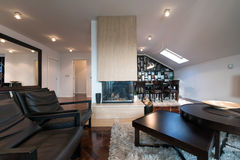 Interior moderno do sótão com a chaminé no meio da sala Fotografia de Stock Royalty Free