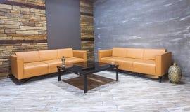 Interior moderno do vintage, sala de visitas, sofá de couro de Brown no revestimento branco do parquet e parede de tijolo Foto de Stock