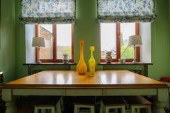 Interior moderno hermoso en la cocina con los colores de las flores y de los floreros, rojos, amarillos y verdes fotos de archivo