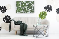 Interior with monstera leaves motif. Metal table in front of sofa with dark blanket in floral living room interior with monstera leaves motif stock image