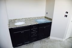 Bathroom Sink in Granite Install. Interior of a new construction home being fitted with a granite bathroom sink stock image
