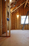 Interior of New Home Construction. An interior view of a new home under construction with exposed wiring and and a ladder in place. Vertical shot Stock Images