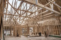 Interior of unfinished new home construction work site walls and roof trusses constructed of 2x4`s. Interior of new home construction work site walls and roof stock image