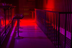 Interior of a nightclub with colorful lighting. Interior of a nightclub with colorful red and purple lighting and a line of stylish bar stool along a reflective Stock Photo