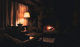 Free Interior Of A Wooden Cozy And Relaxing Cabin With Comfortable Couches, Country Decoration, Dimly Lit By The Fireplace And Lamp. Stock Photo - 168231130