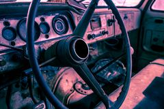Interior of old abandoned truck, grunge background with rusty dashboard and driving wheel.  Stock Photos