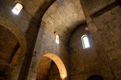 Interior of an old cathedral / church in Europe. Arches, vaulted ceilings and walls lit by lamps stock photo