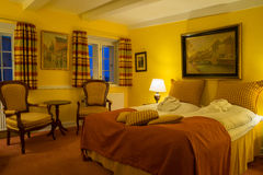 Interior of old fashioned hotel room. Interior of old fashioned vintage hotel room with paintings on the yellow walls at night time at the old Hotel Dagmar, Ribe Royalty Free Stock Photography