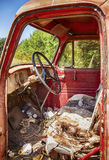 Interior Of Old Red Truck. The interior of an old red truck shows the wear and tear of years of neglect including the box springs and stuffing of the seat and Royalty Free Stock Photos