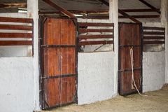 Interior of old rustic stable and head of horse senn through wooden fence stock photo