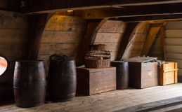 Interior of an old ship. Wooden crates and barrels on board of a restored dutch VOC ship Royalty Free Stock Photos