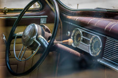 Interior of old vintage abandoned car - logos removed. Front seat steering wheel and faded retro dashboard stock photos