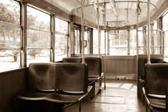Interior of an old vintage tram. Inside is empty, wooden seats. Shadows. Through the glass windows you can see the trees. sepia. Stock Photo
