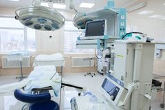 Interior of operating room in modern clinic. Hospital details - Modern surgery room with technology and lamps. Interior of operating room in modern clinic stock photos