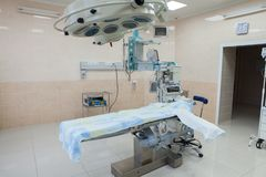 Interior of operating room in modern clinic. Hospital details - Modern surgery room with technology and lamps. Interior of operating room in modern clinic stock photo
