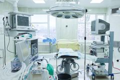 Interior of operating room in modern clinic. Hospital details - Modern surgery room with technology and lamps. Interior of operating room in modern clinic royalty free stock photo