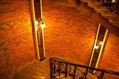 The interior on the order of castle. Beautiful spiral stair, brickwork and warm ceiling lights royalty free stock photos