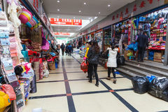 Interior of ordinary Chinese clothing market with people. Hangzhou, China - December 5, 2014: Interior of ordinary Chinese clothing market with walking buyers Royalty Free Stock Photography