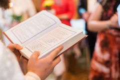 Interior of the Orthodox Church. Orthodox priest during christening baptism reading book Stock Photo