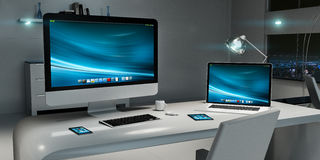 Interior oscuro moderno de la oficina del escritorio con el ordenador y los dispositivos 3D con referencia a Imagenes de archivo