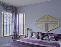 Interior púrpura del ciruelo del dormitorio con la cama de la silla de la ventana Fotos de archivo libres de regalías
