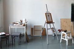 Interior of painting studio of freelance artist. Gypsum head, brushes, pencills, ink and paint bottles with sketchbooks on the table. Easel with watercolor royalty free stock photo
