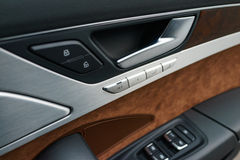 Interior panel of car door. Interior panel of a luxury car door,made with metal and genuine leather Stock Photos