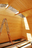 Interior of Partially Built Wooden Cabin. The interior of a partially built small prefabricated wooden cabin on a concrete base. The wall beams are in place and Royalty Free Stock Photography