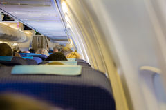 Interior of passenger airplane with people on seats Stock Photography