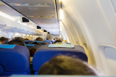 Interior of passenger airplane with people on seats.  Royalty Free Stock Images